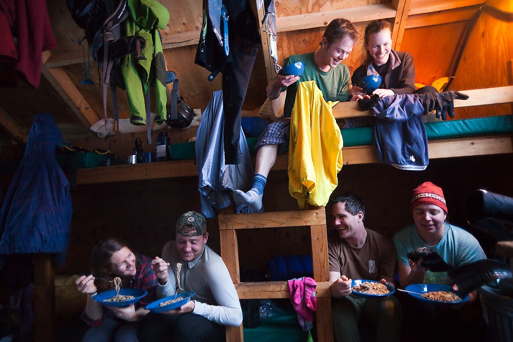 Backcountry skiers eat their pasta dinner in their bed bunks in the North Pole Hut, San Juan Mountains, Colorado.