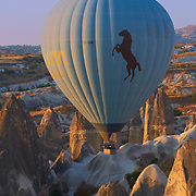 Hot air balloon in the morning among rocks in Cappadocia, Turkey