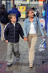 Single mother walking through town centre with young son,