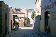 People and bars narrow streets in historic citadel town of Calvi, Corsica, France in late 1950s