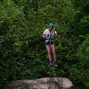 Man with a phone on zipline in Samui beach, Thailand