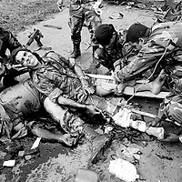 A wounded Government soldier is treated by his collegues next to his dead companion who was killed minutes before when a FARC planted bomb exploded in a bus they were searching. The bus was part of a roadblock built to facilitate the kidnap of Ingrid Betancourt on the 23rd February.<br />
