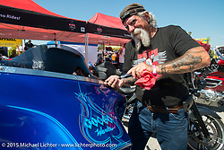 Mailman Kevin O'Brien works the Klock Werks display at  Destination Daytona Harley-Davidson during the 2015 Biketoberfest Rally. FL, USA. October 17, 2015.  Photography ©2015 Michael Lichter.