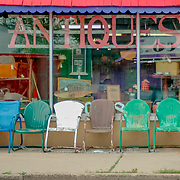 Very colorful antiques storefront with casual lawn chairs.