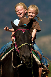 four H Young gleeful girls gallop a horse in Swan Valley Idaho