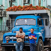Two men with produce truck filled with carrots, waiting for the entrance to the market to open. Havana, Cuba