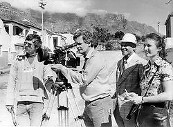 A BBC crew filming in District Six. They are, from left, Mr John Adderley, assistant cameraman, Mr Fred Hamilton, cameraman, Mr Joe Forbes, a member of the Cape Times editorial staff, who showed the team around the area, and Miss Rosalind Erksine, director. The film crew left South Africa yesterday