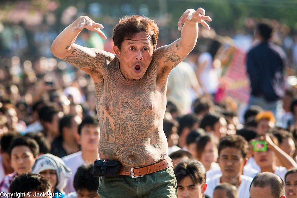 """23 MARCH 2013 - NAKHON CHAI SI, NAKHON PATHOM, THAILAND:  A man with a tiger tattoo rushes the stage at the Wat Bang Phra tattoo festival. Wat Bang Phra is the best known """"Sak Yant"""" tattoo temple in Thailand. It's located in Nakhon Pathom province, about 40 miles from Bangkok. The tattoos are given with hollow stainless steel needles and are thought to possess magical powers of protection. The tattoos, which are given by Buddhist monks, are popular with soldiers, policeman and gangsters, people who generally live in harm's way. The tattoo must be activated to remain powerful and the annual Wai Khru Ceremony (tattoo festival) at the temple draws thousands of devotees who come to the temple to activate or renew the tattoos. People go into trance like states and then assume the personality of their tattoo, so people with tiger tattoos assume the personality of a tiger, people with monkey tattoos take on the personality of a monkey and so on. In recent years the tattoo festival has become popular with tourists who make the trip to Nakorn Pathom province to see a side of """"exotic"""" Thailand. The 2013 tattoo festival was on March 23.    PHOTO BY JACK KURTZ"""