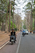 Young Cambodian's ride on a motorcycle along a road with other bikes and cars on Krong Siem Reap Province, Cambodia, South East Asia.