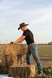 hot cowboy with hay bales on a ranch