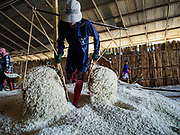 20 FEBRUARY 2019 - BAN LAEM, PHETCHABURI, THAILAND: A salt worker drops her baskets of salt in the warehouse. on one of the first days of the 2019 salt harvest in Ban Laem, Thailand. Ban Laem's salt fields are expanding because salt harvesters in Samut Sakhon and Samut Songkhram,  which are closer to Bangkok, are moving to Ban Laem as their land is turned into industrial parks.      PHOTO BY JACK KURTZ
