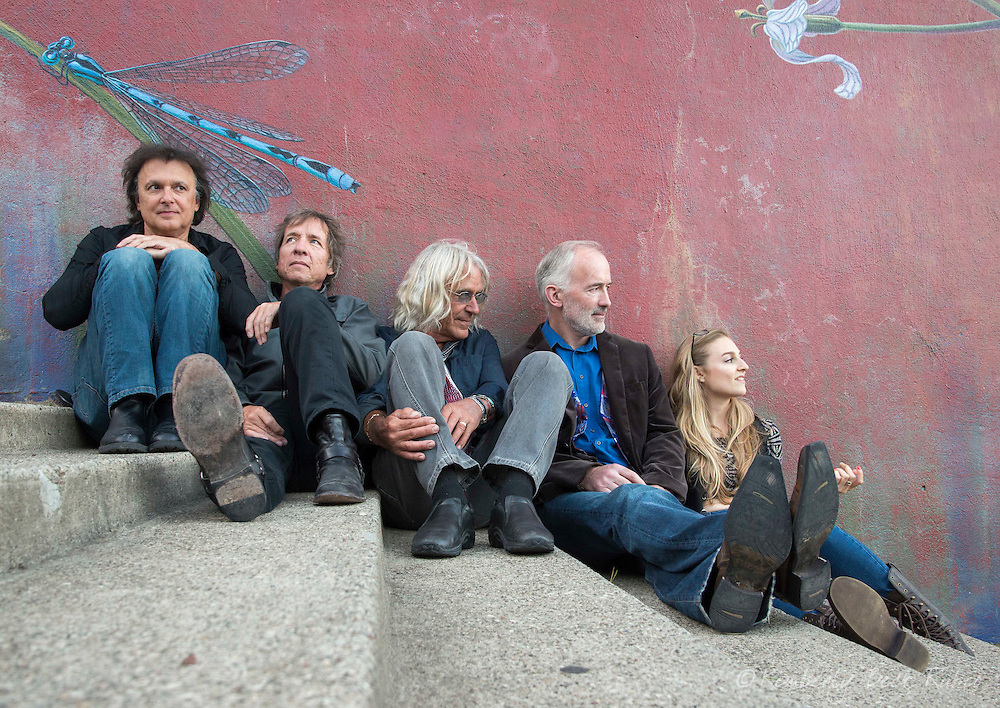Cool friends hanging out, sitting leaning against a mural in San Francisco, California.