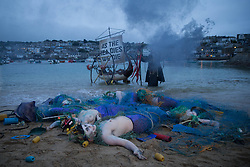 © Licensed to London News Pictures.  11/06/2021. St Ives, UK. Members of the environmental group Sea Rebellion perform on the Town Beach in St Ives, Cornwall as the G7 summit starts today. Photo credit: Marcin Nowak/LNP