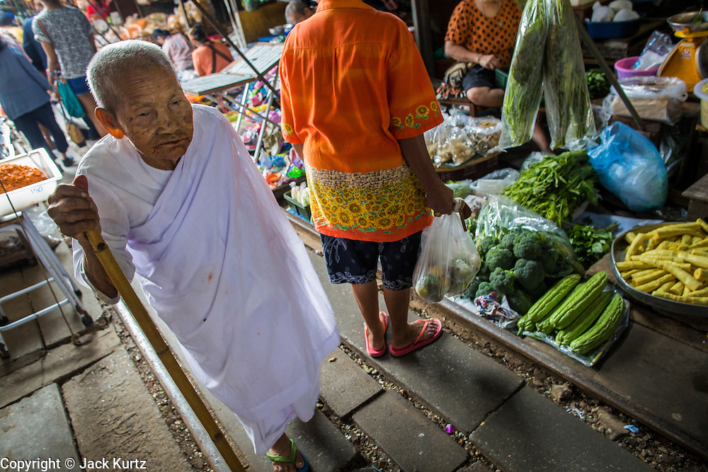 17 JANUARY 2013 - SAMUT SONGKHRAM, SAMUT SONGKHRAM, THAILAND: A Buddhist nun in the market in Samut Songkhram. Four trains each day make the round trip from Baan Laem, near Samut Sakhon, to Samut Songkhram, the train chugs through market eight times a day (coming and going). Each time market vendors pick up their merchandise and clear the track for the train, only to set up again when the train passes. The market on the train tracks has become a tourist attraction in this part of Thailand and many tourists stop to see the train on their way to or from the floating market in Damnoen Saduak.    PHOTO BY JACK KURTZ