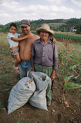 Family group with grandfather; father and son standing with sacks of corn on a farm near Jibacoa; Cuba,