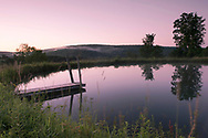 A still pond at sunrise at Firefly Farm in Hauverville, New York State, U.S.A.
