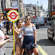 A lady is holding a bus stop sign outside Green park station, London, UK August 4 2018.