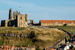 Suns set behind the Gothic ruins of Whitby Abbey overlooking the North Sea on the East Cliff above Whitby in North Yorkshire, England