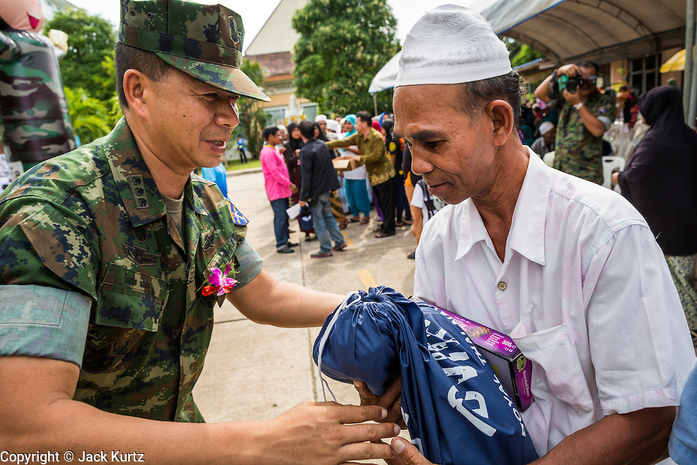 07 JULY 2013 - NARATHIWAT, NARATHIWAT, THAILAND:   Royal Thai Marine officers hand out rice and snacks to Thai Muslim civilians during a civil affairs program Sunday. Royal Thai Marines in Narathiwat province held a special ceremony Sunday in advance of Ramadan. They presented widows, orphans and indigent people with extra rice and food as a part of the Thai government's outreach to resolve the Muslim insurgency that has wracked southern Thailand since 2004. The Holy Month of Ramadan starts on about July 9 this year. Muslims are expected to fast from dawn to dusk, engage in extra prayers, recitation of the Quran and perform extra acts of charity during Ramadan. It is the holiest month of the year for Muslims.  PHOTO BY JACK KURTZ