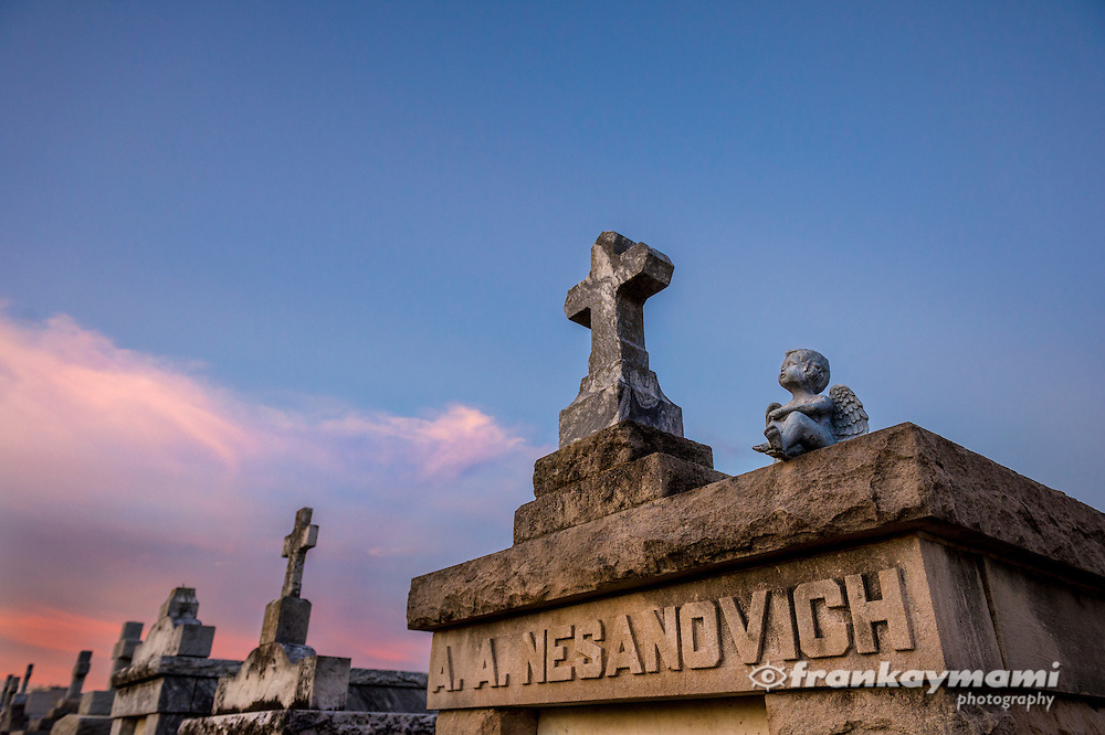 Statues stand among the sunset in St. Louis #3 Cemetery in New Orleans, LA.