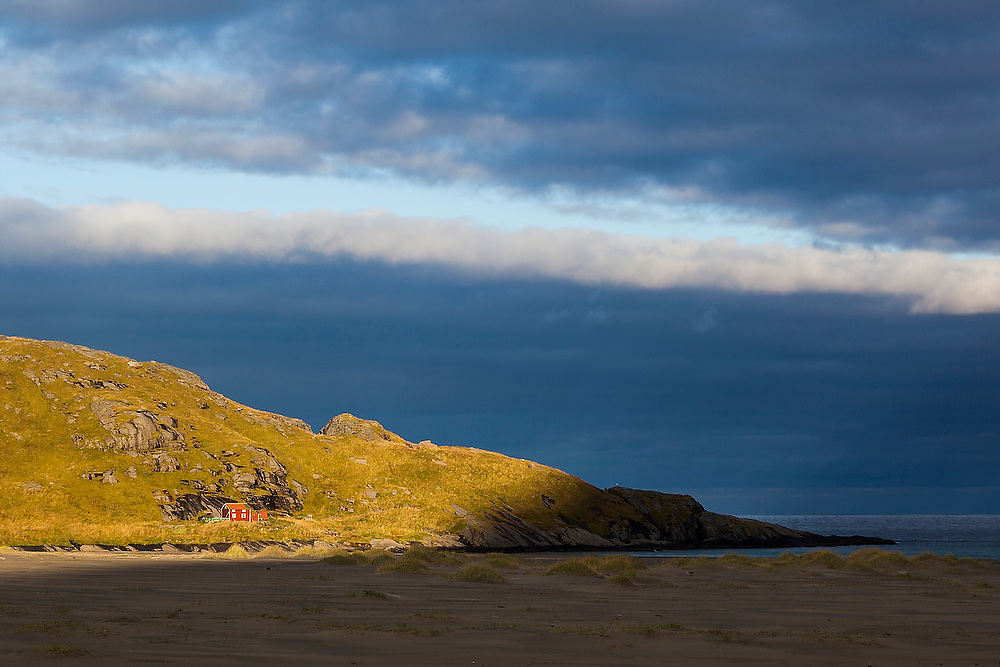 A shaft of morning light illuminates a lone cabin above Bunes Beach, Moskenesoya, Lofoten Islands, Norway.