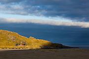 A shaft of morning light illuminates a lone cabin above Bunes Beach, Moskenesoya, Lofoten Islands, Norway.