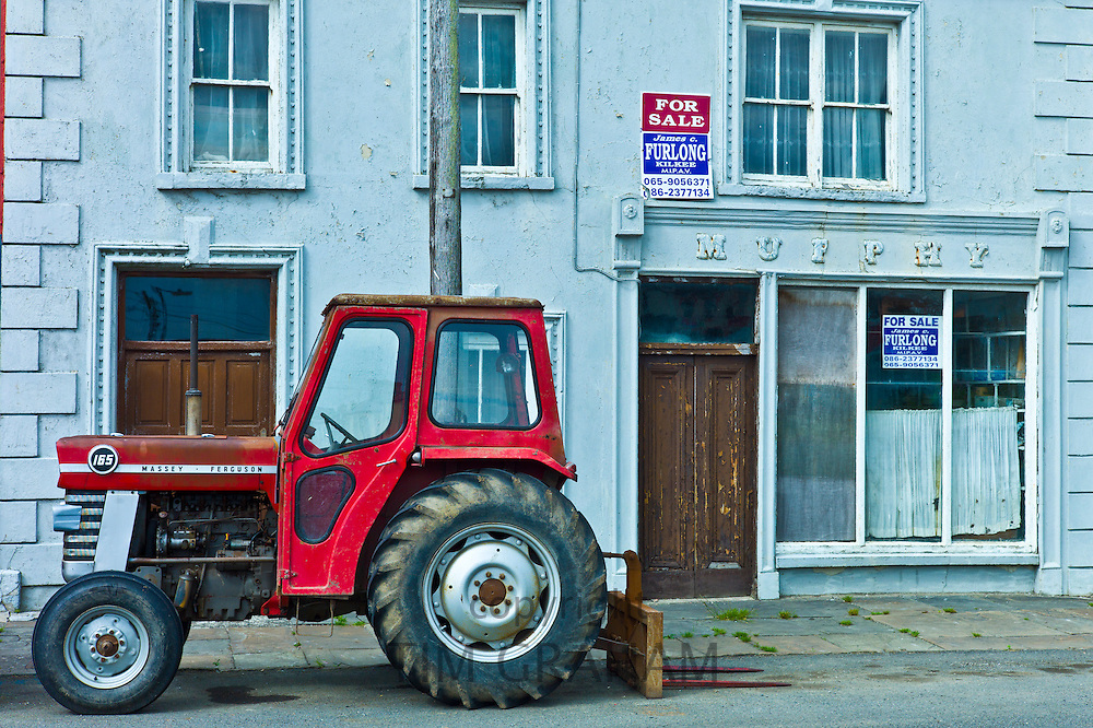 Tractor parked at  Murphy shop with estate agent For Sale boards in, Kilkee, County Clare, West of Ireland