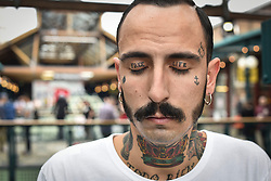 © licensed to London News Pictures. 26/09/2014<br /> The 10th London International Tattoo Convention, one of the most prestigious body art conventions in the world, brought together 400 of the best tattoo artists to thousands of admirers at Tobacco Dock. Other attractions and alternative performances included burlesque, sword swallowing, striptease dancers, fire-dancers and trapeze performers. Pictured. Artist Matteo from Italy.<br /> Photo credit : Ian Whittaker/LNP