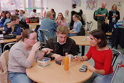 Teenage girl with physical disability sitting at table with friends in college canteen,