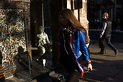 A young male admires a sexy girl watched be the statuette of a small woman credited to the 19th century Florence-born artist Raffaello Romanelli. In afternoon sunlight, the girl is on the corner of Albermarle Street and Piccadilly, London W1, Westminster. Oblivious to the attention on her by an unknown man, the girl in blue walks fast along the pavement listening to her portable device, a career girl in the fast modern city - the opposite of the classical figure in the rug and carpet shop window who bares a breast while wearing jewellery. The female form is on show to the male of the species.