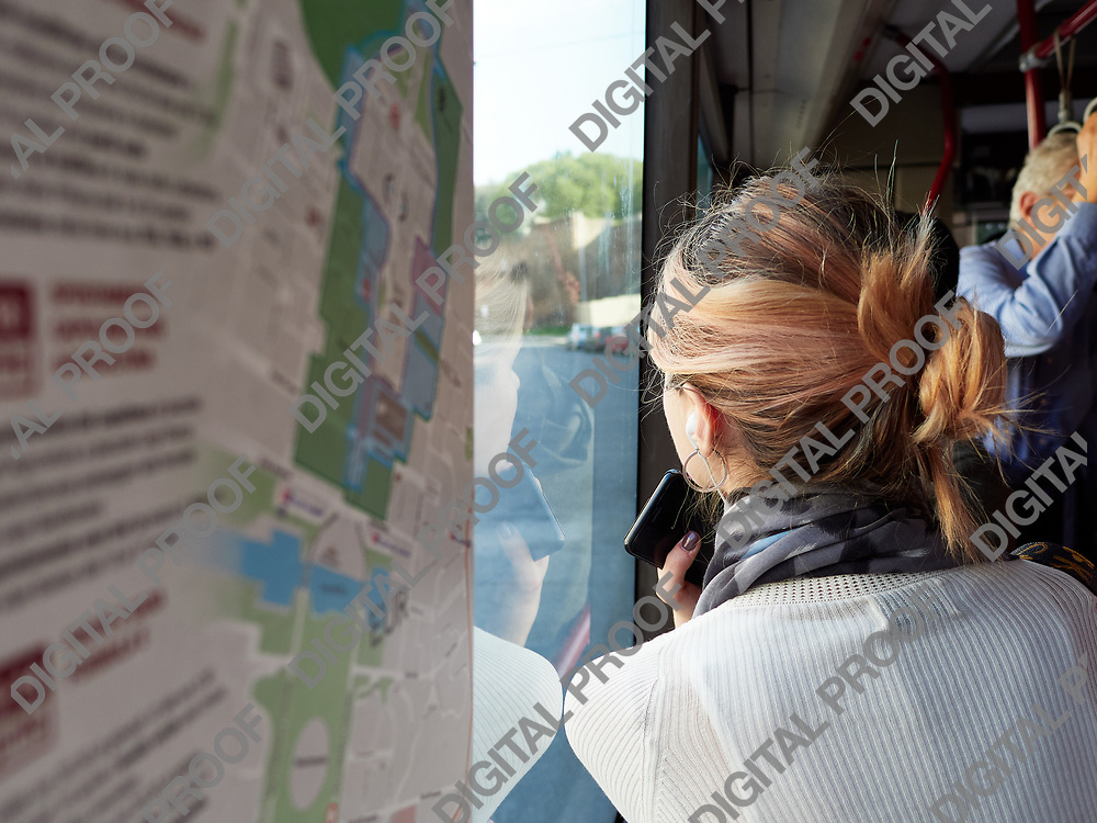 Back view of woman holding smartphone and riding in public bus looking out of window, Italy.