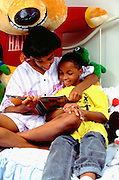 African American age 13 and 9 year old sister and brother doing homework in bed.  St Paul Minnesota USA