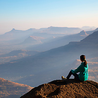 Girl enjoying the morning light at Mount kalsubai, Maharashtra, India.
