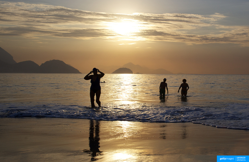 Early morning swimmers at sunrise on Copacabana beach, Rio de Janeiro,  Brazil. 9th July 2010. Photo Tim Clayton..The beaches of Rio de Janeiro, provide the ultimate playground for locals and tourists alike. Beach activity is in abundance as beach volley ball, football and a hybrid of the two, foot volley, are played day and night along the length and breadth of Rio's beaches. .Volleyball nets and football posts stretch along the cities coastline and are a hive of activity particularly at it's most famous beaches Copacabana and Ipanema. .The warm waters of the Atlantic Ocean provide the ideal conditions for a variety of water sports. Walkways along the edge of the beaches along with exercise stations and cycleways encourage sporting activity, even an outdoor gym is available at the Parque Do Arpoador overlooking the ocean. .On Sunday's the main roads along the beaches of Copacabana, Leblon and Ipanema are closed to traffic bringing out thousands of people of all ages to walk, run, jog, ride, skateboard and cycle more than 10 km of beachside roadway. .This sports mad city is about to become a worldwide sporting focus as they play host to the world's biggest sporting events with Brazil hosting the next Fifa World Cup in 2014 and Rio de Janeiro hosting the Olympic Games in 2016..