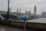 During a downpour, an afternoon of heavy rainfall in London, a wet man stands in a puddle overlooking the River Thames and parliament, from Londons Southbank, on 7th June 2016. In the weeks before Britain goes to the polls to vote whether to stay or leave the EU community of nations, the man represents a poignant pause in the choices faced by Britons during turbulent times.