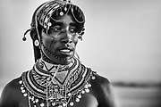 A Samburu warrior with long hair covered in goat fat and ochre standing on a hilltop overlooking Lake Turkana, black and white,Lake Turkana, Loiyangalani,Kenya, Africa
