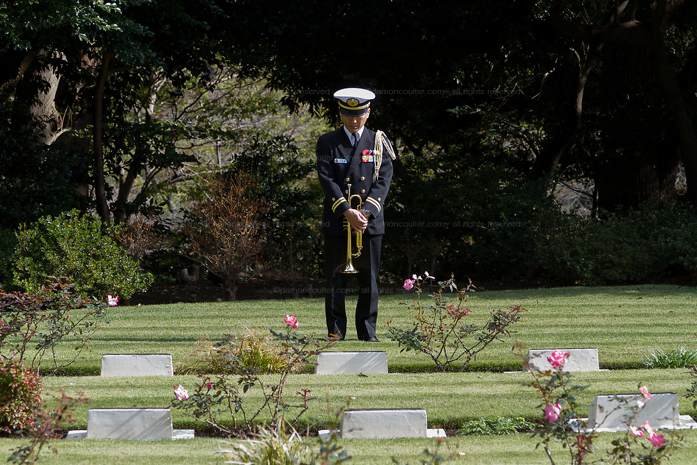 Bugler, Lieutenant Hiromi Watanabe contemplates the graves of fallen servicemen and women during the Remembrance Sunday ceremony at the Hodogaya, Commonwealth War Graves Cemetery in Hodogaya, Yokohama, Kanagawa, Japan. Sunday November 11th 2018. The Hodagaya Cemetery holds the remains of more than 1500 servicemen and women, from the Commonwealth but also from Holland and the United States, who died as prisoners of war or during the Allied occupation of Japan. Each year officials from the British and Commonwealth embassies, the British Legion and the British Chamber of Commerce honour the dead at a ceremony in this beautiful cemetery. The year 2018 marks the centenary of the end of the First World War in 1918.