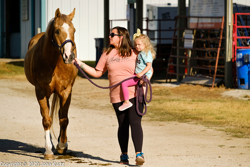 16 JULY 2020 - BOONE, IOWA: KAYLA COOK carries her daughter, HARPER COOK, 2 years old, and leads their horse, Blaze across the fairgrounds on the first day of the Boone County Fair in Boone. Summer is county fair season in Iowa. Most of Iowa's 99 counties host their county fairs before the Iowa State Fair. In 2020, because of the COVID-19 (Coronavirus) pandemic, many county fairs were cancelled, and most of the other county fairs were scaled back to concentrate on 4H livestock judging. Boone county scaled back its fair this year. The Iowa State Fair was cancelled completely. Boone County Emergency Management did not approve going ahead with the fair, and has advised anyone who goes to the fair to take precautions and monitor themselves for symptoms of the Coronavirus.           PHOTO BY JACK KURTZ