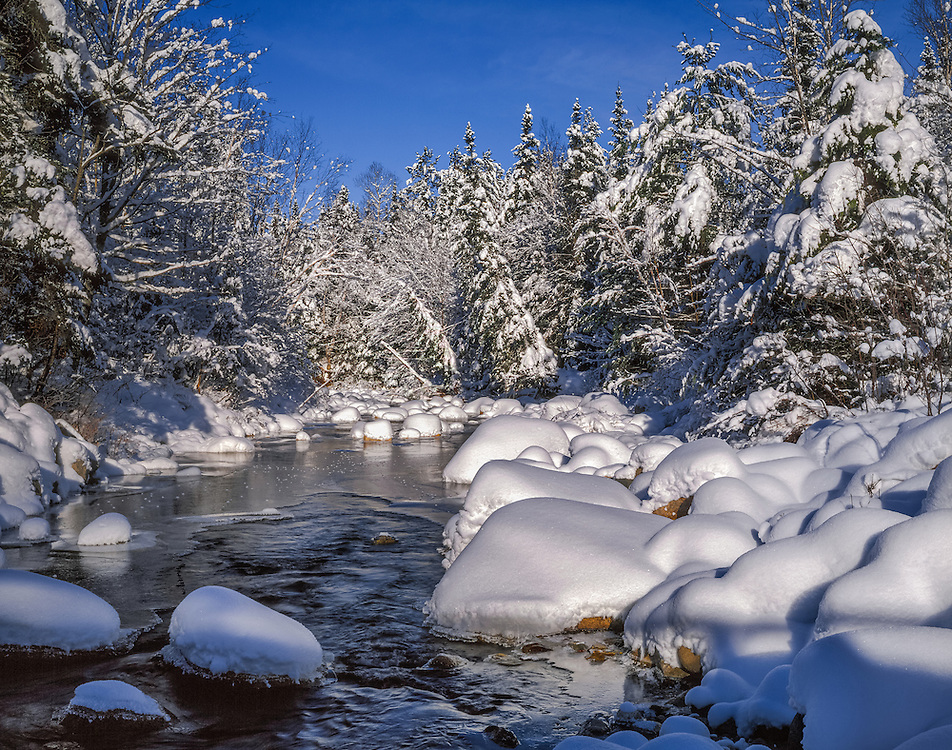 Heavy snow covers rocks at waters edge and spruce, under a deep blue sky, White Mountain National Forest, Bethlehem, NH
