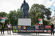 Windrush campaigners protest in front of the statue of Sir Winston Churchill in Parliament Square on 23rd June 2021 in London, United Kingdom. The campaigners, who had marched from the Home Office to the House of Commons in order to deliver a letter, are calling for a new independent body, and not the Home Office, to administer the scheme intended by the government to compensate them for the violation of their rights. Many legal residents who came to the UK from the Caribbean lost their homes, jobs and other rights after having been targeted by the Home Office.