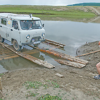 MONGOLIA. Driver of a van for an archaeology expedition drives off wooden ferry across a river between Rinchenlhumbe and Tsaagan Nuur.