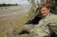 Self portrait of photographer Tim Laman with inner-tube blind on mangrove mudflats.
