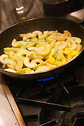 Apple slices fried in Butter melting in a frying pan, bubble or foam. on a cast iron gas stove. Gas fire. The Dolly Irigoyen - famous chef and TV presenter - private restaurant, Buenos Aires Argentina, South America Espacio Dolli