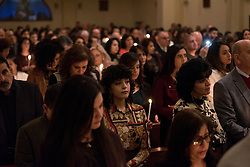 20 April 2019, Jerusalem: Congregant pray with candles in hand during Holy Saturday service at Saint James' Church in Beit Hanina, Jerusalem.
