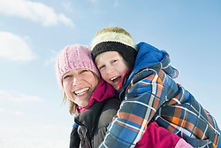 Mother giving piggy back ride to son, smiling, portrait, Bavaria, Germany