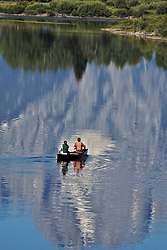 A canoe paddling through the reflection of Mt. Moran at Oxbow Bend in Grand Teton National Park