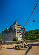 """Trebuchets were probably the most powerful catapult employed in the Middle Ages. The most commonly used ammunition were stones, but """"darts and sharp wooden poles"""" could be substituted if necessary. The most effective kind of ammunition though involved fire, such as """"firebrands, and deadly Greek Fire"""". Trebuchets came in two different designs: Traction, which were powered by people, or Counterpoise, where the people were replaced with """"a weight on the short end"""". The most famous historical account of trebuchet use dates back to the siege of Stirling Castle in 1304, when the army of Edward I constructed a giant trebuchet known as Warwolf, which then proceeded to """"level a section of [castle] wall, successfully concluding the siege"""".<br /> <br /> A catapult is a ballistic device used to launch a projectile a great distance without the aid of gunpowder or other propellants – particularly various types of ancient and medieval siege engines. A catapult uses the sudden release of stored potential energy to propel its payload. Most convert tension or torsion energy that was more slowly and manually built up within the device before release, via springs, bows, twisted rope, elastic, or any of numerous other materials and mechanisms. The counterweight trebuchet is a type of catapult that uses gravity.<br /> <br /> In use since ancient times, the catapult has proven to be one of the most persistently effective mechanisms in warfare. In modern times the term can apply to devices ranging from a simple hand-held implement (also called a """"slingshot"""") to a mechanism for launching aircraft from a ship.<br /> <br /> The earliest catapults date to at least the 4th century BC with the advent of the mangonel in ancient China, a type of traction trebuchet and catapult. Early uses were also attributed to Ajatashatru of Magadha in his war against the Licchavis. Early Greek catapults emerged around the 1st century BC."""