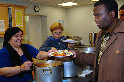 Volunteers serve curry to refugees and asylum seekers in a soup kitchen at a church hall; Bradford Yorkshire UK