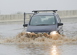 © Licensed to London News Pictures. 30/05/2013<br /> <br /> Saltburn, Cleveland, United Kingdom<br /> <br /> A motorist makes his way through deep floods as heavy overnight rain causes flooding in Saltburn on the A174 coast road near to the Ship Inn on the seafront in the town.<br /> <br /> Photo credit : Ian Forsyth/LNP