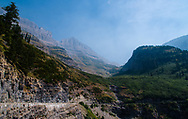 Smoke fills the sky between mountains and drifts through a canyon at Glacier National Park, Montana as viewed from Going-to-the-Sun Road